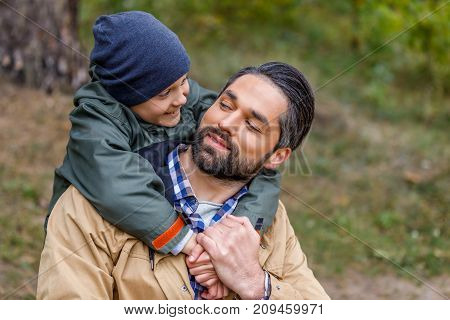 happy father and son hugging at lake