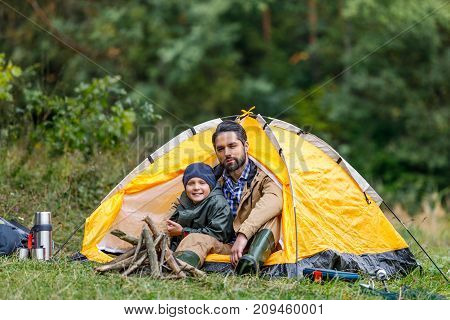 Father And Son Sitting In Tent