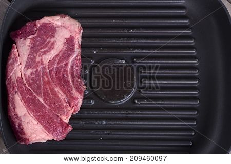 Close-up Top View Of Raw Beef Steak On Grill Pan. Copy Space. Receipt Concept