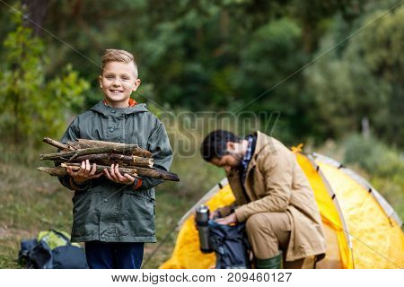Son Holding Sticks For Campfire