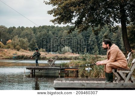 Father And Son Fishing On Piers