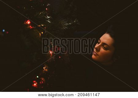 Pretty Young Girl Dreaming Of Christmas As She Rests. A Beautiful Woman Lies Under A Christmas Tree