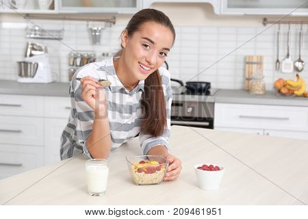 Young woman in pajamas eating oatmeal in kitchen