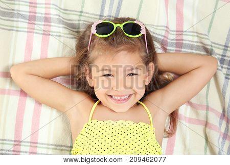 Adorable little girl in swimsuit lying on beach blanket