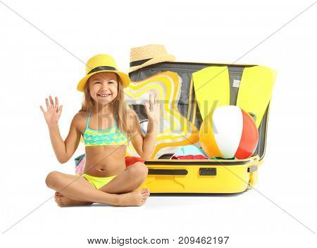 Adorable little girl sitting near suitcase on white background