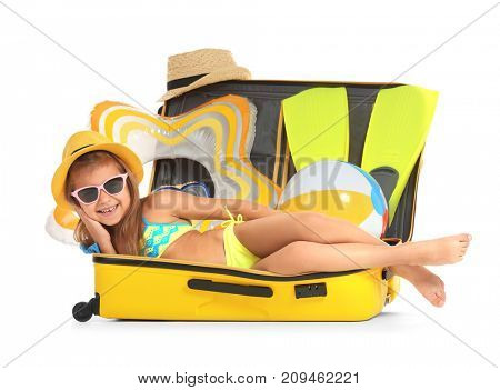 Adorable little girl lying in suitcase on white background