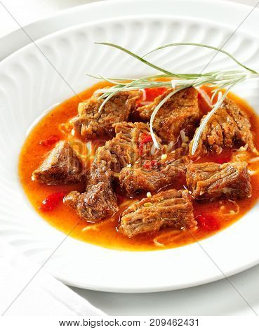 Delicious beef stew served in a red sauce.