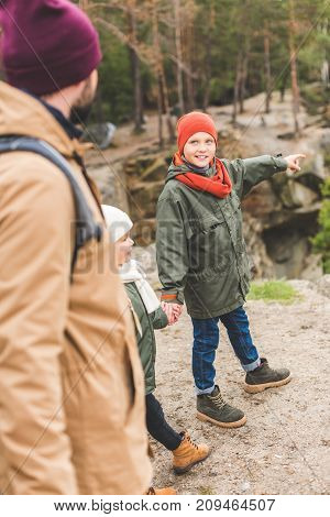 selective focus of little smiling boy pointing away while standing on rock together with family in autumn forest