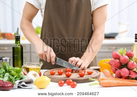 Man cutting tomatoes on wooden board