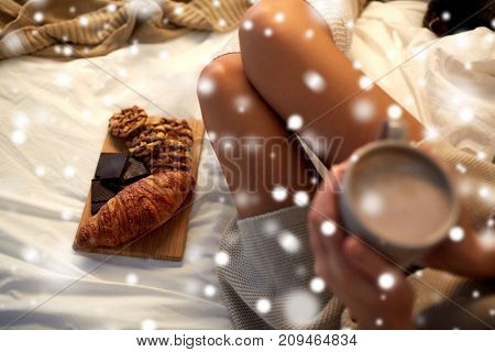 winter, coziness, leisure and people concept - close up of young woman holding cup of coffee or cacao drink with sweets and baking in bed at cosy home over snow