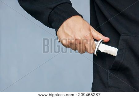 Hand From The Pocket Of The Black Jacket Pulls Out A Folding Knife Close Up.