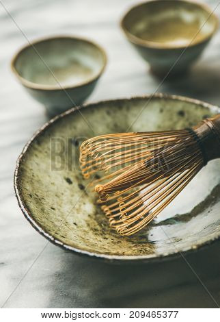 Flat-lay of Japanese tools for brewing matcha tea. Matcha powder in tin can, Chasen bamboo whisk, Chawan bowl, cups for ceremony, grey background, selective focus