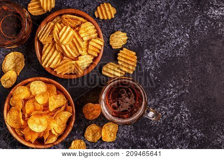 Beer And Crispy Potato Chips On Stone Background.