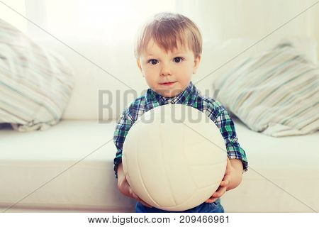 childhood and people concept - happy little baby boy with ball at home