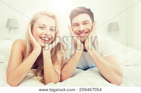 people, rest, love, relationships and happiness concept - happy couple lying in bed at home