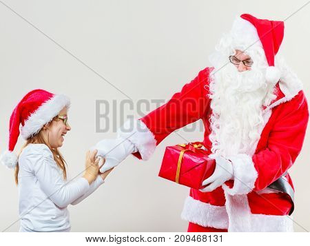 Christmas holiday concept. Man wearing Santa Claus costume fighting with girl in christmassy hat for present.