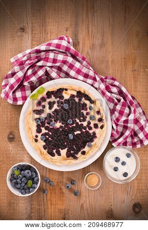 Blueberry tart with brown sugar on white dish.
