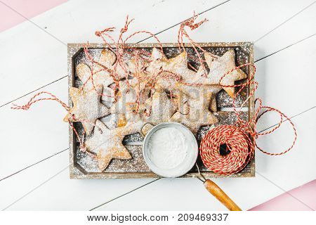 Christmas homemade gingerbread star shaped cookies with sugar powder in sieve and red decoration rope in wooden tray over white wooden background, top view, horizontal composition