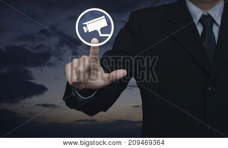 Businessman pressing cctv camera icon over sunset sky Business security concept