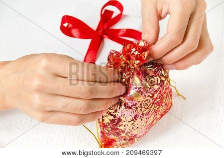 Women's hands tie a small bag with gifts next to a gift box on the table. White background.