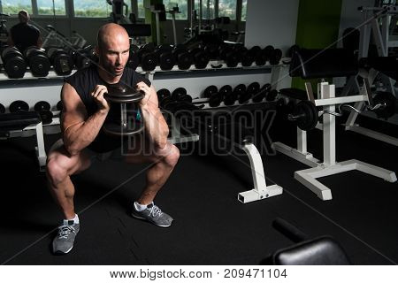 Muscular Man Exercising Quadriceps With Dumbbells
