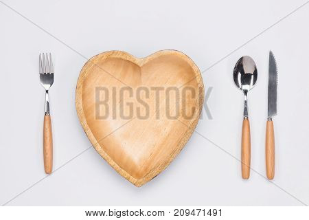 Wooden plate in shape of heart table knife and fork on white background.