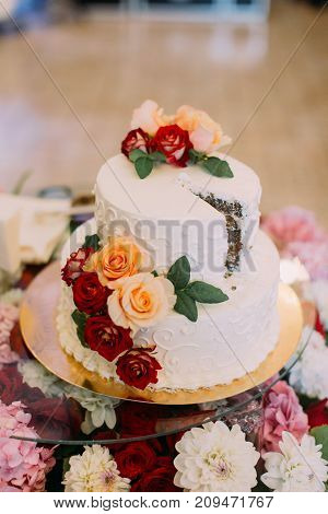Close-up view of the wedding cake decorated with colourful roses