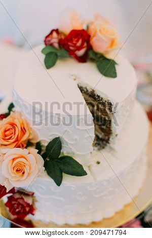 Colourful roses decorate the white wedding cake