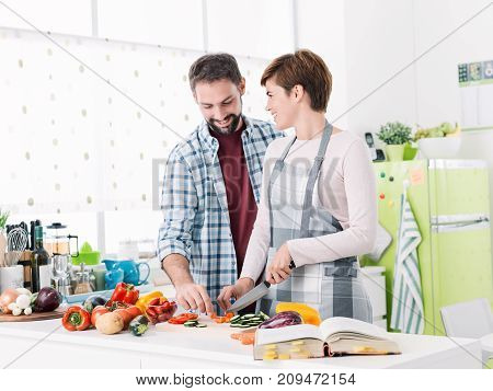 Romantic loving couple cooking together at home the woman is slicing vegetables and the man is hugging her