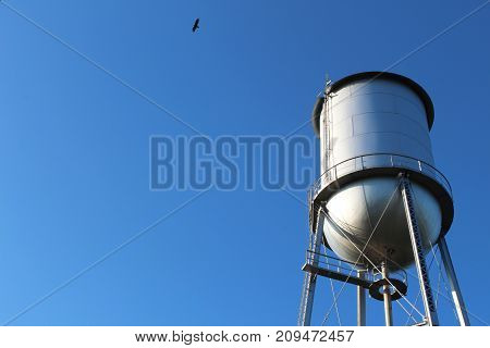 View of an old style water tower against a deep blue sky,