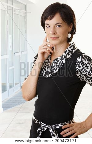 Businesswoman portrait. Young businesswoman standing in office, smiling.