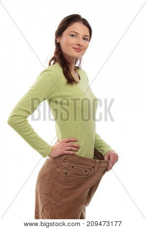 Teenager girl wearing several sizes too big trousers, holding it up with hand, looking at camera, smiling. Isolated on white.