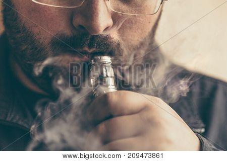 Vaping man holding e-cigarette mod or vape device, vapor looks like smoke, close up, toned