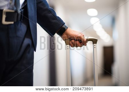 Unrecognizable businessman walking with luggage in a hotel corridor.Close up.