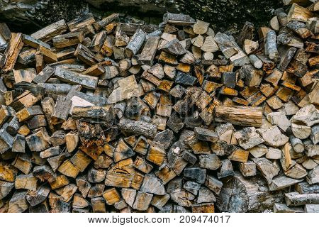 Pile of firewood, dry firewood background, natural wood forest energy concept