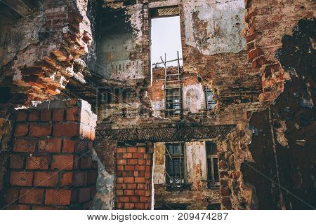 Ruined building, old ruins of brick house broken by war, earthquake or other natural disaster. Demolition building concept, toned