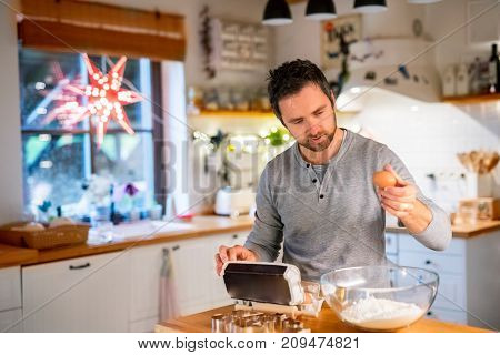 Man making cookies at home. Father baking gingerbread Christmas cookies, preparing the dough.