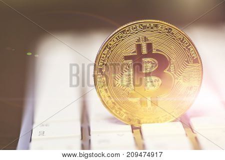 Cryptocurrency golden bitcoin coin on white keyboard - symbol of crypto currency - electronic virtual money for web banking and international network payment, selective focus, light filter, toned