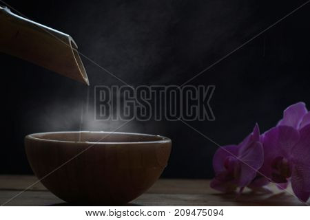 Steam Over A Bowl Into Which Water Is Poured From A Bamboo Stem In The Night Dusk, Orchid Flowers