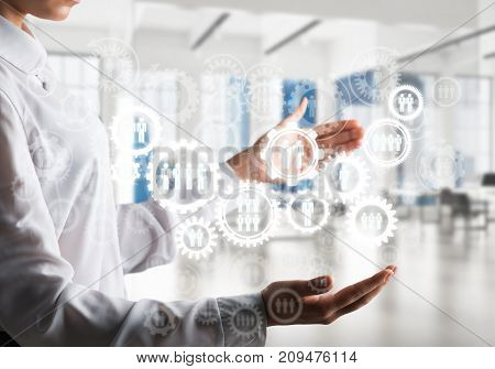 Business woman in white shirt keeping white social gear icons in hands with office view on background. Mixed media.