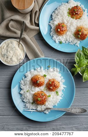 Plates with delicious meatballs and rice on wooden table