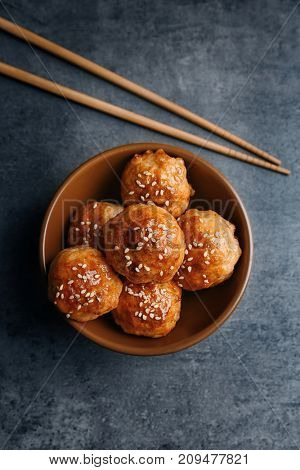 Bowl with delicious meatballs and chopsticks on table