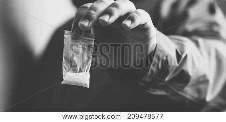 Drug dealer selling drugs junkie. Drug abuse concept and overdose concept. Mans hand holds plastic packet with cocaine powder, selective focus, black and white photo poster