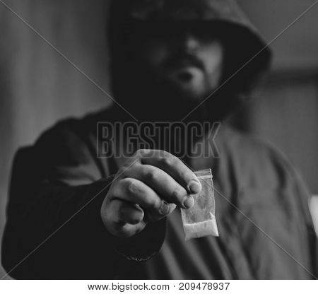Drug dealer selling drugs junkie. Drug abuse concept and overdose concept. Mans hand holds plastic packet with cocaine powder, selective focus, black and white photo