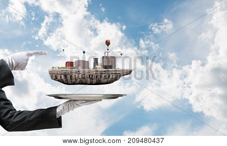 Cropped image of waitress's hand in white glove presenting modern city block on metal tray and pointing on it with blue cloudy skyscape on background. 3D rendering.