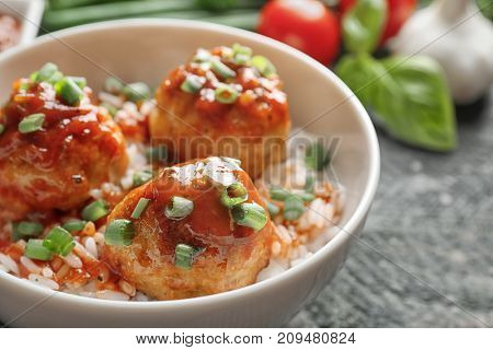 Delicious meatballs with rice and sauce in bowl on table
