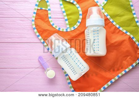 Composition with milk formula and baby bibs on wooden background