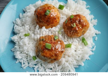 Plate with delicious meatballs and rice, closeup