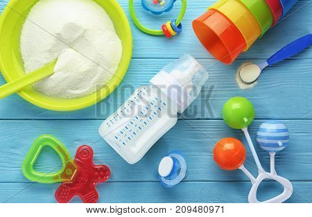 Composition with baby milk formula, rattles and pacifier on wooden background