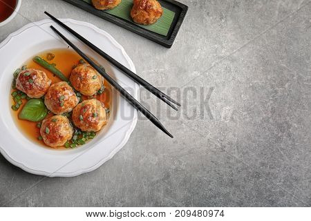 Delicious meatballs with sauce in plate on table